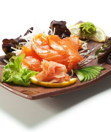 tare: Salmon Sashimi - Sake (fresh raw salmon) on Daikon (White Radish). Garnished with Ginger, Wasabi, Seaweed, Cucumber, Salad Leaf and Lemon Stock Photo