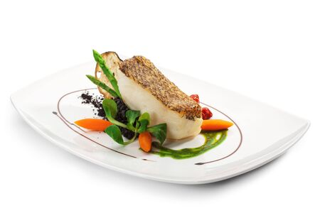 black dish: Chile Sea Bass (black sea bass) served with Black Risotto, Herbs and Vegetables Stock Photo