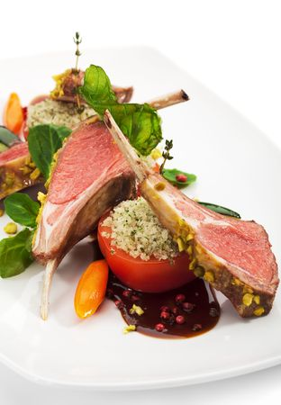 rack of lamb: Roasted Lamb Chops with Pistachio. Garnished with Vegetables and Basil Stock Photo