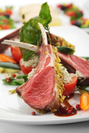 lamb chop: Roasted Lamb Chops with Pistachio. Garnished with Vegetables and Basil Stock Photo