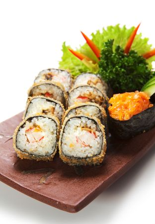 Japanese Dish - Tempura Maki Sushi (Deep Fried Roll made of Smoked Eel, Crab Meat and Cream Cheese inside) with Spicy Salmon (sake) Gunkan Sushi. Garnished with Salad Leaf and Parsley Stock Photo