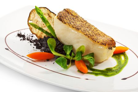 risotto: Chile Sea Bass (black sea bass) served with Black Risotto, Herbs and Vegetables Stock Photo