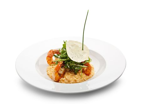 italian PEOPLE: Risotto with Tiger Prawns and Rucola. Served with Parmesan Chip Stock Photo