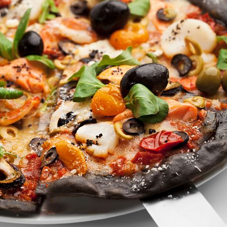 dough: Black Ink Dough Pizza with Seafood, Black and Green Olives, Dried Tomato and Salad Leaves Stock Photo