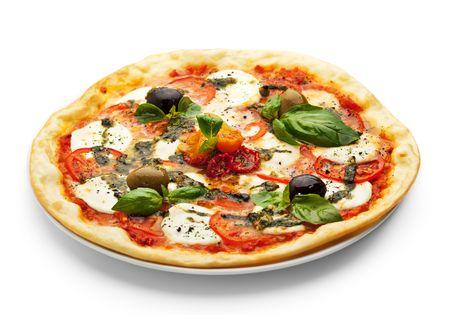 pizza: Pizza con queso mozzarella, tomate fresco y salsa de pesto. Adornado con tomate seco, verde y aceitunas negras y hojas de albahaca Foto de archivo