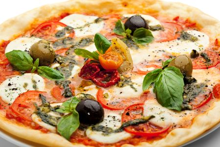 mozzarella: Pizza with Mozzarella Cheese and Fresh Tomato and Pesto Sauce. Garnished with Dried Tomato, Green and Black Olives and Basil Leaves Stock Photo