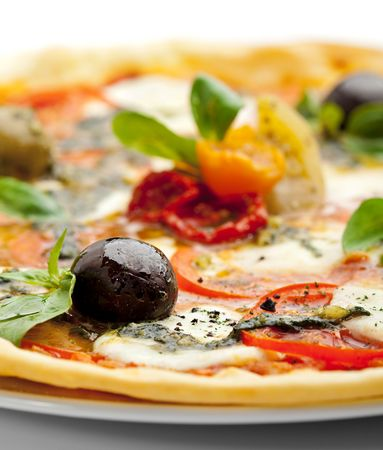 Pizza with Mozzarella Cheese and Fresh Tomato and Pesto Sauce. Garnished with Dried Tomato, Green and Black Olives and Basil Leaves Stock Photo