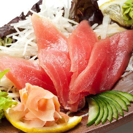 tare: Tuna Sashimi - Maguro (fresh raw tuna) on Daikon (White Radish). Garnished with Ginger, Wasabi, Seaweed, Cucumber, Salad Leaf and Lemon