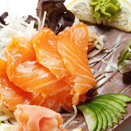 Salmon Sashimi - Sake (fresh raw salmon) on Daikon (White Radish). Garnished with Ginger, Wasabi, Seaweed, Cucumber, Salad Leaf and Lemon photo