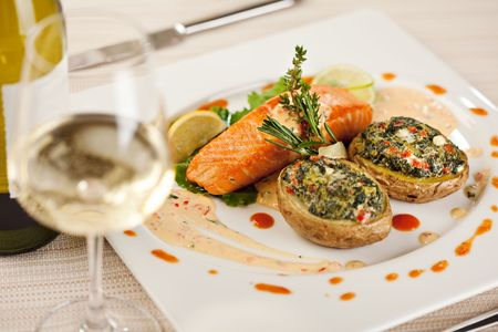 stuffed fish: Baked Jacket Potato and Salmon Steak. Served with White Wine Stock Photo