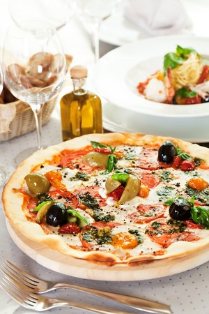 restaurant setting: Pizza with Mozzarella Cheese, Fresh Tomato and Pesto Sauce. Served at Restaurant Table Stock Photo