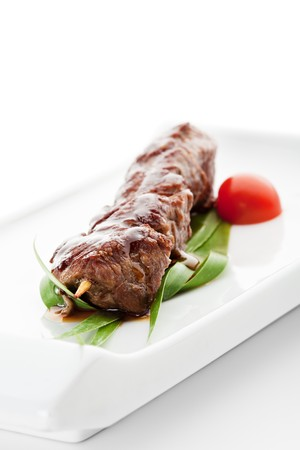 Grilled Veal Meat  Garnished with Cherry Tomato and Green Leaf photo