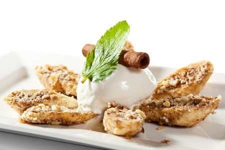 banana slice: Scoop of Ice Cream. Garnished with Banana Slice with Nuts, Fresh Mint and Cinnamon Stick