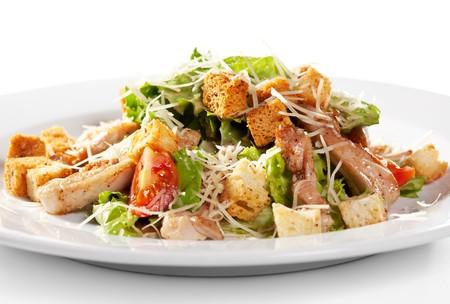 Ensalada César con carne. Comprende hojas de ensalada de Romaine y vestidas con queso parmesano de migas de pan