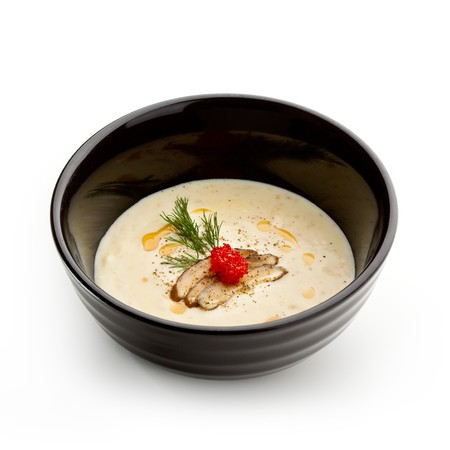 Black Bowl of Cheese Cream Soup with Bacon and Caviar photo
