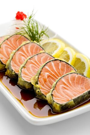 Wrapped in Nori Salmon Fillet Deep Fried. Garnished with Lemon and Herbs photo