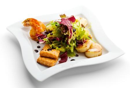 plato de comida: Mariscos - gambas, mar de vieiras, calamares y salm�n. Adornado con Fresh Leaf Raw de ensalada.