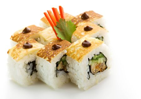spring roll: Omelet Maki Sushi - Roll made of Smoked Eel, Cucumber and Spring Onion inside. Topped with Tamago (Japanese Omelet) and Sauce Stock Photo