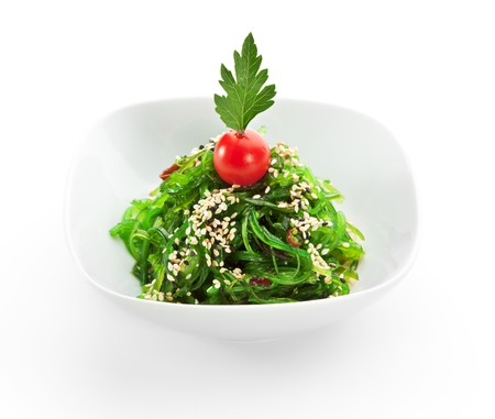 Pickled Seaweed with Nut Sauce. Garnished with Sesame Seeds and Cherry TOmato photo