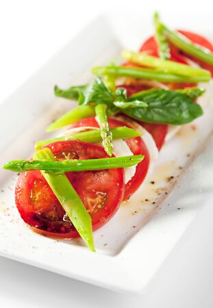 Caprese Salad - Salad with Tomatoes, Mozzarella Cheese, Green Asparagus and Basil Leaf photo