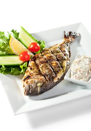 Fried Fish (Dorado) Garnished with Lemon, Tomato, Cucumber and Sauce photo