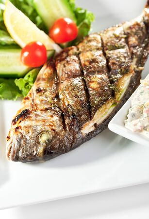 Fried Fish (Dorado) Garnished with Lemon, Tomato, Cucumber and Sauce photo
