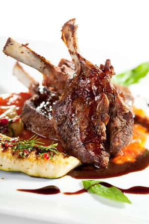 Roasted Lamb Chops on Tomato Sauce Garnished with Vegetables and Basil photo