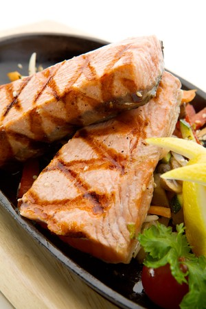 Grilled Foods - Salmon Steak with Vegetables. Garnished with Lemon and Parsley photo
