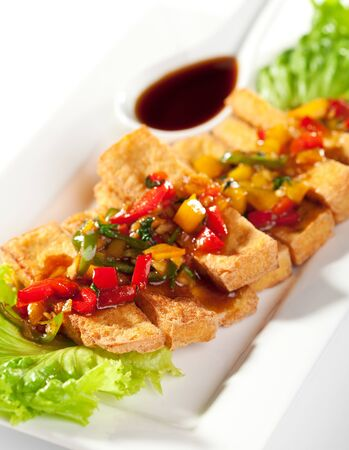 Deep Fried Tofu Topped with Fried Vegetables. Garnished with Sauce and Fresh Salad Leaf photo