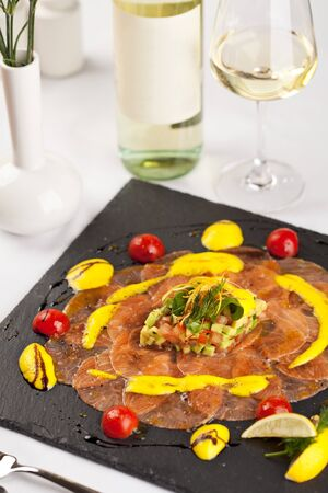 Salmon Carpaccio on Black Dish with White Wine Stock Photo - 8006259