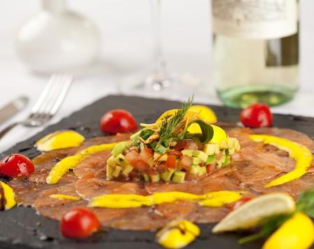 Salmon Carpaccio on Black Dish with White Wine Stock Photo - 8006141
