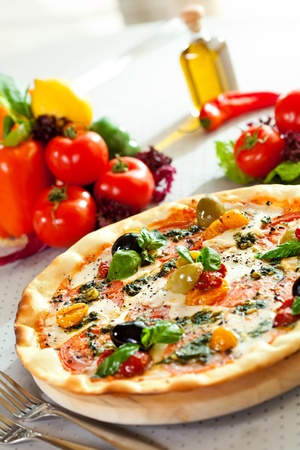 Pizza with Mozzarella Cheese, Fresh Tomato and Pesto Sauce. Served at Restaurant Table photo