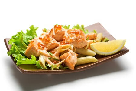 penne: Pasta Penne with Salmon Slice and Red Caviar. Garnished on Salad Leaf with Cream Cheese Sauce and Lemon Slice