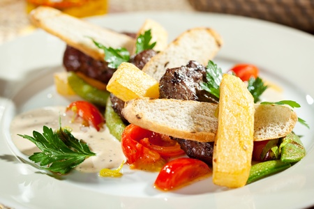 Hot Meat Dishes - Beef Medallions with French Fries, Vegetables and Sauce photo