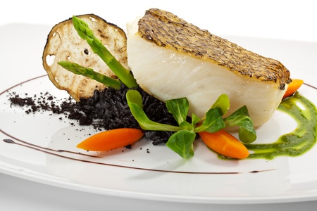 cooked fish: Chile Sea Bass (black sea bass) served with Black Risotto, Herbs and Vegetables Stock Photo