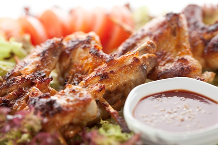 Hot Meat Dishes - Fried Chicken Wings with Salad Leaves, Tomatoes and Spicy Sauce photo