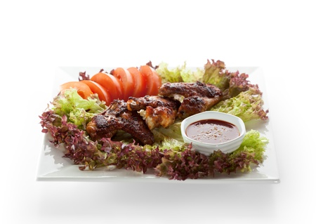 Hot Meat Dishes - Fried Chicken Wings with Salad Leaves, Tomatoes and Spicy Sauce Stock Photo - 11417649