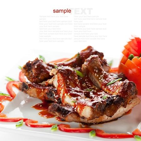 barbecue ribs: Platos calientes de carne - costillas a la barbacoa con tomates y salsa picante Foto de archivo