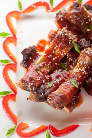 american cuisine: Hot Meat Dishes - BBQ Ribs with Tomatoes and Spicy Sauce Stock Photo