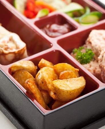 Japanese Meal in a Box (Bento) - Potatoes, Steamed Cutlet and Sweet Fruit Sushi photo