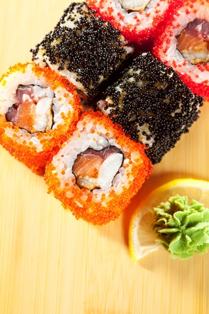 Japanese Cuisine - Sushi Roll with Tuna, Salmon, Eel and Shrimp inside. Tobiko (Flying Fish Roe) outside photo