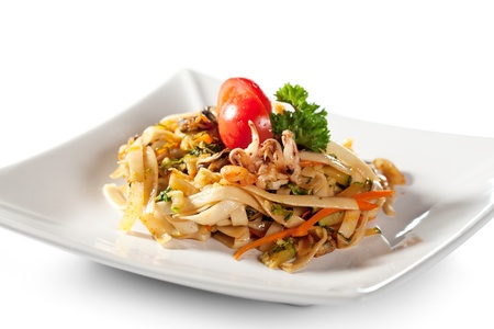 Japanese Cuisine - Udon (thick wheat noodles) with Seadood and Vegetables. Garnished with Cherry Tomato and Parsley photo
