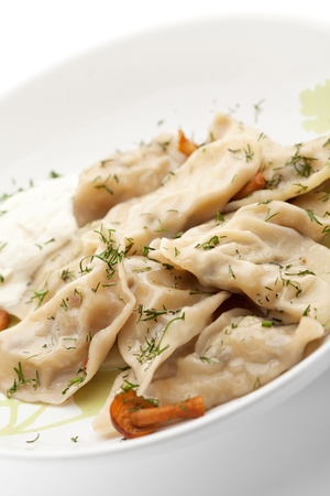 Dumplings with Potato and Mushrooms  Garnished with Dill and Sour Cream Sauce photo