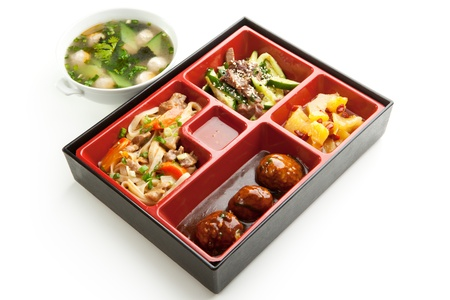 bento: Japanese Meal in a Box  Bento  - Meat Cutlets and Noodles with Cucumbers Salad and Dessert Stock Photo
