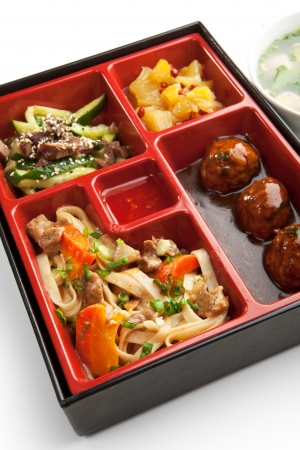 bento box: Japanese Meal in a Box  Bento  - Meat Cutlets and Noodles with Cucumbers Salad and Dessert Stock Photo