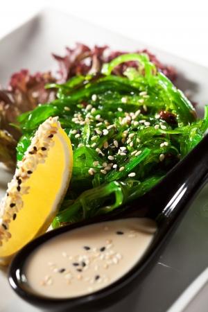Cocina Japonesa - Ensalada de algas con Chuka salsa de nueces servidos con limón y sésamo Foto de archivo