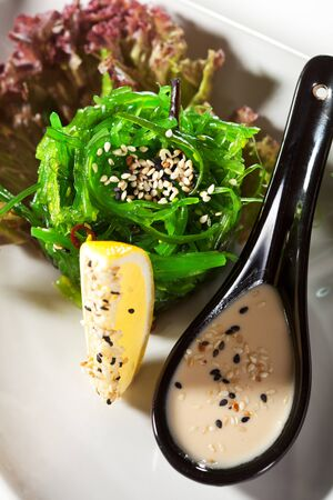 Japanese Cuisine - Chuka Seaweed Salad with Nuts Sauce  Served with Lemon and Sesame Stock Photo - 13676863