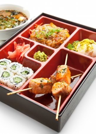 Japanese Meal in a Box  Bento  - Salad, Skewered Salmon and Sushi Roll and Dessert photo