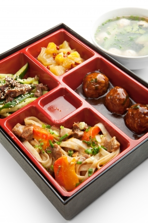 Japanese Meal in a Box  Bento  - Meat Cutlets and Noodles with Cucumbers Salad and Dessert photo
