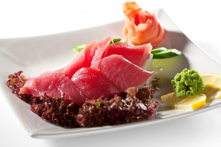 Tuna Sashimi - Sliced Raw Tuna on Daikon  White Radish  with Seaweed and Cucumber photo